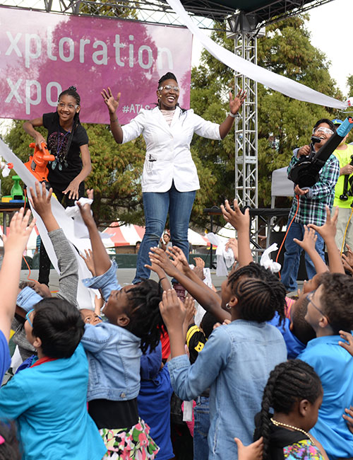 Smiling lady with hands in the air on stage in front of an audience of children.