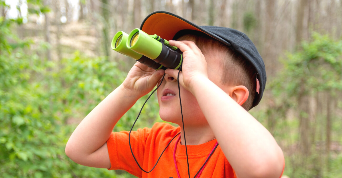 Young boy in an orange t-shirt and gray cap looking through a pair of green binoculars.