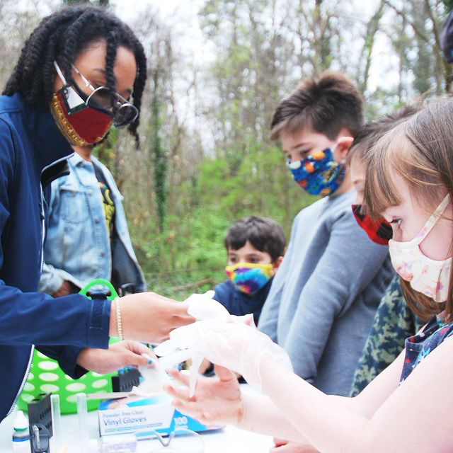 An adult female doing a science project outside with multiple children wearing masks during the 2021 Atlanta Science Festival.